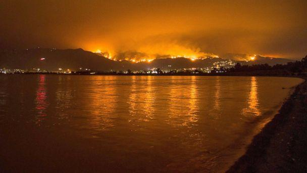 PHOTO: Flames from the Holy Fire are reflected in Lake Elsinore as the wildfire burns in the Cleveland National Forest, in Lake Elsinore, Calif., Aug. 8, 2018. (Robyn Beck/AFP/Getty Images)