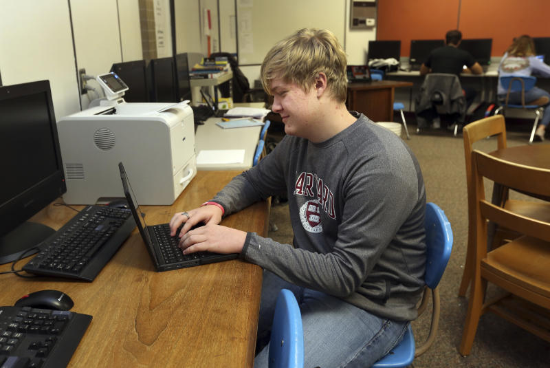 Braxton Moral, 16, sits in the computer room of Ulysses High School in Ulysses, Kan., on Wednesday, Dec. 12, 2018. The senior uses the computer room to work on his Harvard studies for approximately three hours each school day. He is projected to graduate from Harvard and then graduate from Ulysses later in May 2019. (Sandra J. Milburn/The Hutchinson News via AP)