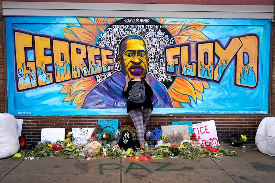 Damarra Atkins pays respect to George Floyd at a mural at George Floyd Square, Friday, April 23, 2021, in Minneapolis.