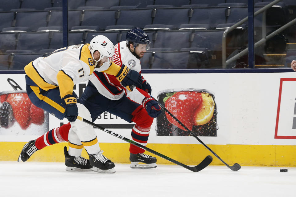 Nashville Predators Ben Harpur, left, and Columbus Blue Jackets' Oliver Bjorkstrand chase a loose puck during the second period of an NHL hockey game Saturday, Feb. 20, 2021, in Columbus, Ohio. (AP Photo/Jay LaPrete)