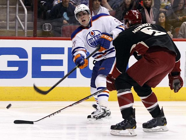 Edmonton Oilers left wing David Perron (57) shoots in front of Phoenix Coyotes defenseman Connor Murphy (5) in the first period of an NHL hockey game, Tuesday, Dec. 31, 2013, in Glendale, Ariz. (AP Photo/Rick Scuteri)