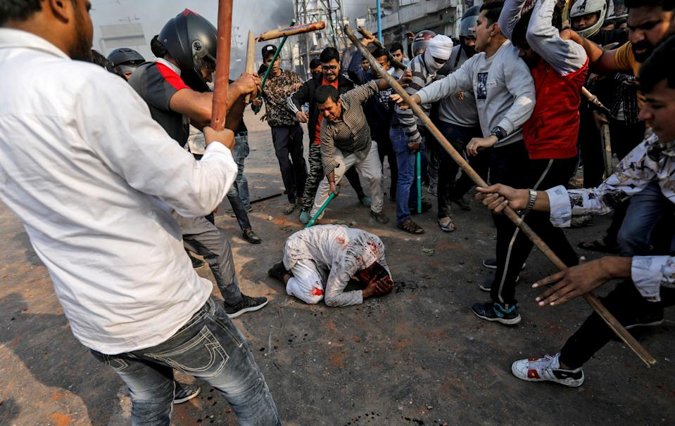 """SENSITIVE MATERIAL. THIS IMAGE MAY OFFEND OR DISTURB  A group of men chanting pro-Hindu slogans, beat Mohammad Zubair, 37, who is Muslim, during protests sparked by a new citizenship law in New Delhi, India, February 24, 2020. Reuters photographer Danish Siddiqui: """"It had been a winter of protests in India, with hundreds of thousands taking to the streets against a new citizenship law that many felt discriminated against the country's Muslim minority. In February, competing protests between those against the law and its supporters turned into communal riots with violent clashes. A source called me to tell me that trouble had broken out at one of the protest sites. Within a few minutes of arriving on the scene, it became clear this was a more dangerous situation, with heavy stone-pelting, and throwing of Molotov cocktails and bottles of acid. Shadowing lines of heavily outnumbered police, I noticed more than a dozen people ranging from teenagers to old men assaulting a Muslim man in white clothes. Using sticks, cricket stumps, plastic pipes and metal rods, they brutally beat the man. Blood flowed from his head as he went down on his knees. The attack was over in less than a minute, as Muslims on the other side of the road started throwing stones. The man, whom I later came to know as Mohammad Zubair, lay on the road alone as stones, bricks and Molotov cocktails flew over him. Zubair suffered serious injuries all over his body as well as internally but was lucky to survive and is still recovering. 'They saw I was alone, they saw my cap, beard, shalwar kameez (traditional outfit) and saw me as a Muslim,' Zubair said to me when I met him a couple of days later. 'They just started attacking, shouting slogans. What kind of humanity is this?'"""" REUTERS/Danish Siddiqui/File photo     SEARCH """"POY STORIES 2020"""" FOR THIS STORY. SEARCH """"WIDER IMAGE"""" FOR ALL STORIES. TPX IMAGES OF THE DAY"""
