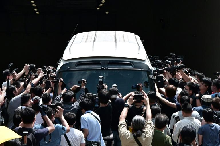 Members of the media surround a prison van carrying the four leaders sentenced to jail