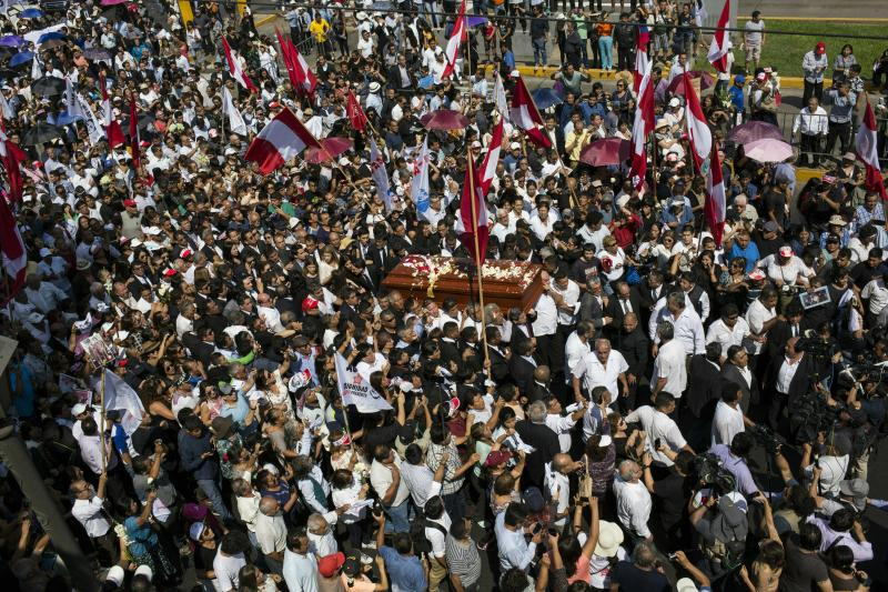 People carry the coffin of Peru's late President Alan Garcia through the street during his funeral procession in Lima, Peru, Friday, April 19, 2019. Garcia shot himself in the head and died Wednesday as officers waited to arrest him in a massive graft probe that has put the country's most prominent politicians behind bars and provoked a reckoning over corruption. (AP Photo/Rodrigo Abd)
