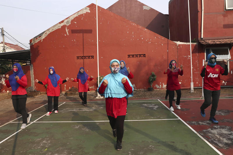 Indonesian women wearing face mask as a precaution against the new coronavirus outbreak perform their group exercise in Tangerang on the outskirts of Jakarta, Indonesia, Saturday, June 27, 2020. (AP Photo/Tatan Syuflana)