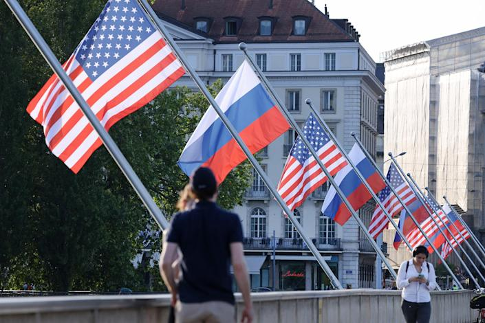 Image: People walk under Russian and American flags on a bridge in the city center prior to a meeting between U.S. President Joe Biden and Russian President Vladimir Putin (Sean Gallup / Getty Images)