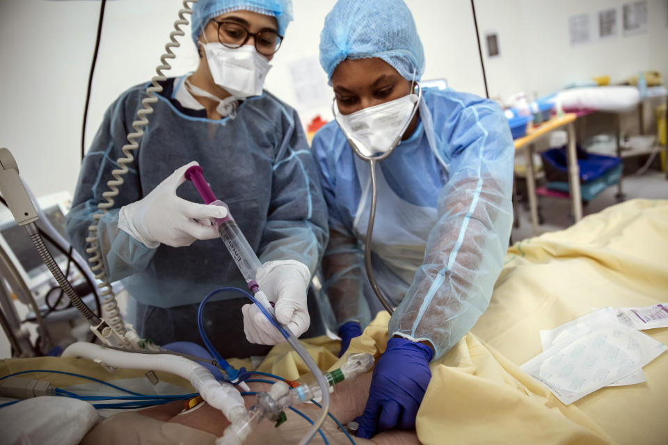 Nurses Nadia Boudra, left, and Yvana Faro, right, care for a patient inside an operating room now used for unconscious COVID-19 patients at Bichat Hospital, AP-HP, in Paris, Thursday, April 22, 2021. France still had nearly 6,000 critically ill patients in ICUs this week as the government embarked on the perilous process of gingerly easing the country out of its latest lockdown, too prematurely for those on pandemic frontlines in hospitals. President Emmanuel Macron's decision to reopen elementary schools on Monday and allow people to move about more freely again in May, even though ICU numbers have remained stubbornly higher than at any point since the pandemic's catastrophic first wave, marks another shift in multiple European capitals away from prioritizing hospitals. (AP Photo/Lewis Joly)
