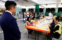 A local candidate looks at officials counting votes at a polling station in Kowloon Tong, Hong Kong