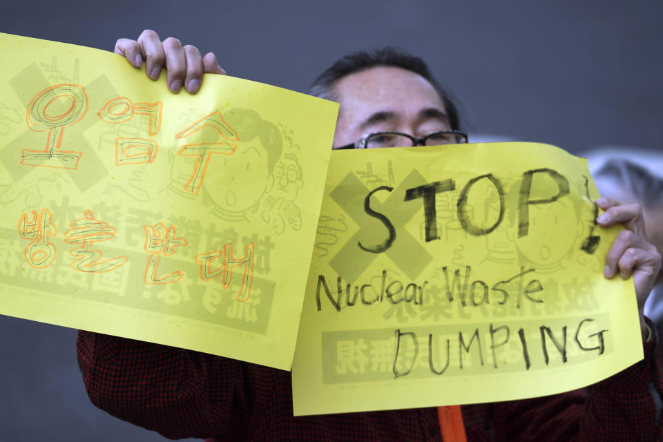 "A man holds placards that read ""Oppose to release contaminated water,"" left, and ""Stop Nuclear Waste Dumping"" during a protest rally against government's decision, outside the prime minister's office in Tokyo Tuesday, April 13, 2021. Japan's government decided Tuesday to start releasing treated radioactive water from the wrecked Fukushima nuclear plant into the Pacific Ocean in two years, an option fiercely opposed by fishermen, residents and Japan's neighbors. (AP Photo/Eugene Hoshiko)"