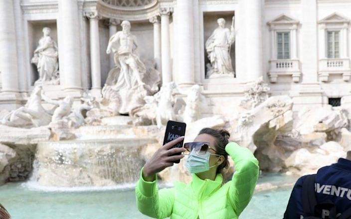 A tourist wearing a face mask at the Trevi Fountain in Rome - Alessia Pierdomenico/BLOOMBERG