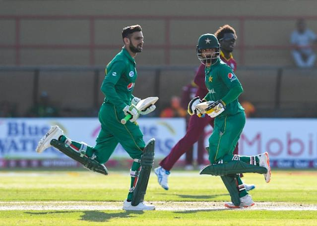 Shoaib Malik (L) and Mohammad Hafeez (C) of Pakistan 100 run partnership during the 3rd and final ODI match between West Indies and Pakistan at Guyana National Stadium, Providence, Guyana, April 11, 2017.The fielder is Chadwick Walton (R) of West Indies (AFP Photo/Randy BROOKS)