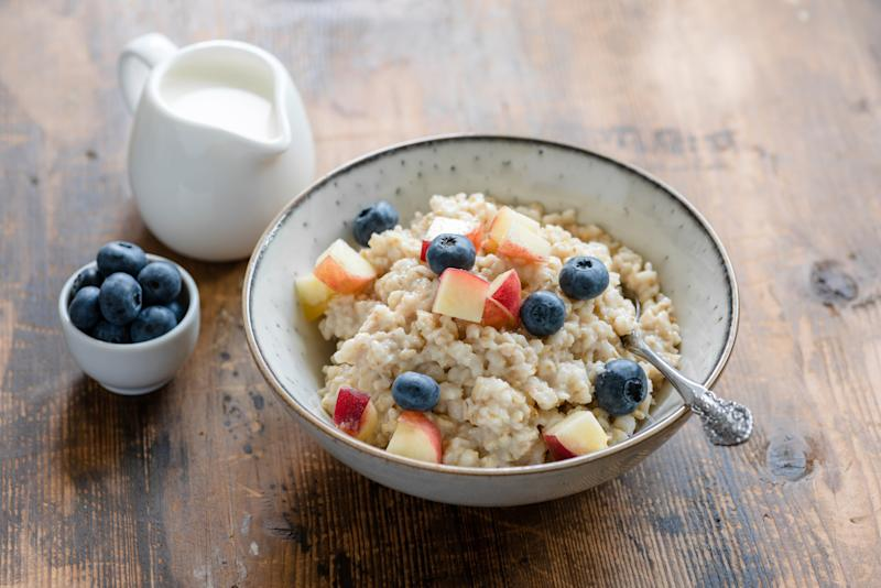 Oatmeal porridge with blueberries and peach. Porridge bowl. Healthy breakfast food. Rustic style
