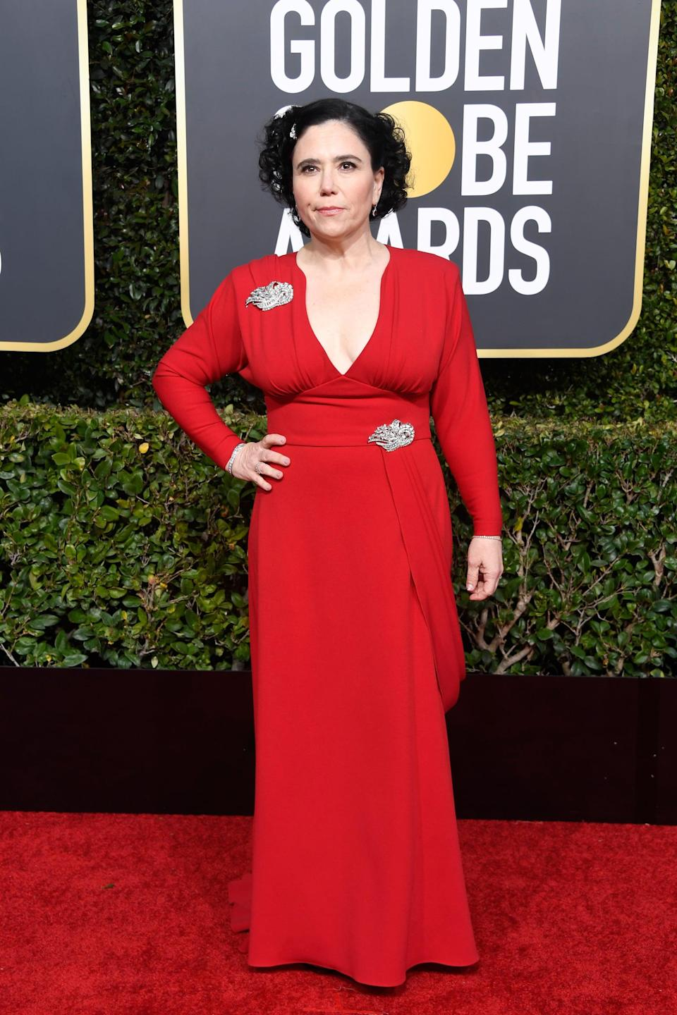 <p>Wearing a red dress with brooches.</p>
