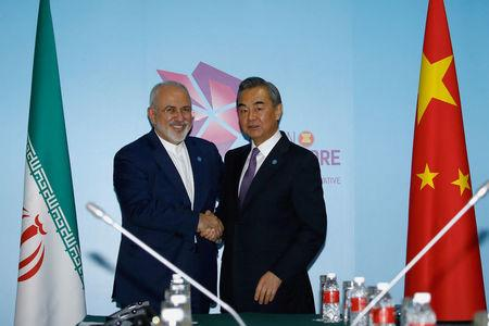 FILE PHOTO - Iran's Foreign Minister Mohammad Javad Zarif and China's Foreign Minister Wang Yi shake hands at a bilateral meeting on the sidelines of the ASEAN Foreign Ministers' Meeting in Singapore