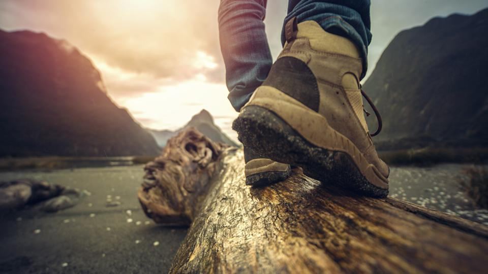 Low angle view of man's legs and hiking boots standing on tree log.