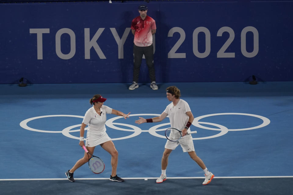 Anastasia Pavlyuchenkova and Andrey Rublev, of the Russian Olympic Committee, react to a point during the mixed doubles gold medal match of the tennis competition at the 2020 Summer Olympics, Sunday, Aug. 1, 2021, in Tokyo, Japan. (AP Photo/Seth Wenig)