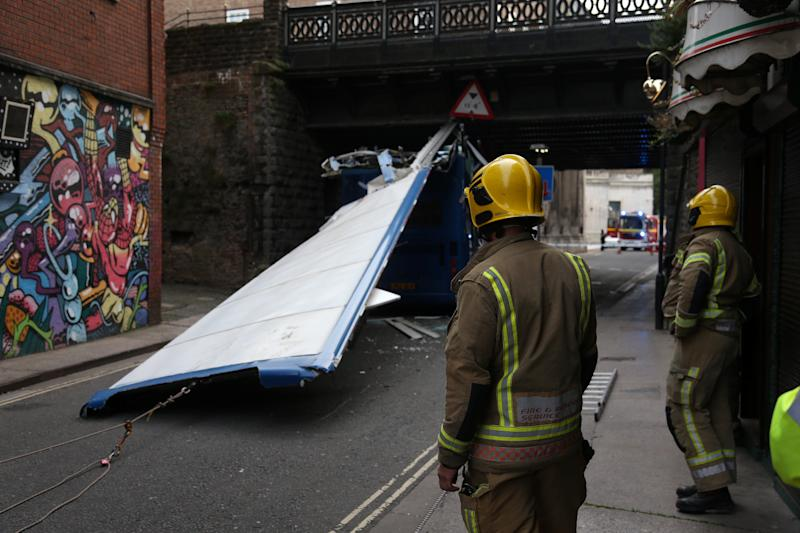 Investigators survey the scene in Bristol city centre where the bus's roof was left behind the vehicle in the street. (SWNS)
