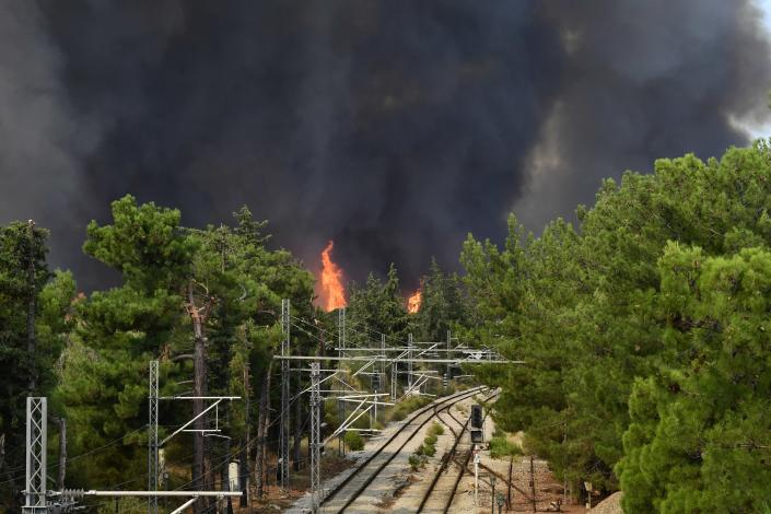 Flames burn near the railway lines in Tatoi area, northern Athens, Greece, Tuesday, Aug. 3, 2021. Greece Tuesday grappled with the worst heatwave in decades that strained the national power supply and fueled wildfires near Athens and elsewhere in southern Greece. As the heat wave scorching the eastern Mediterranean intensified, temperatures reached 42 degrees Celsius (107.6 Fahrenheit) in parts of the Greek capital. (AP Photo/Michael Varaklas)