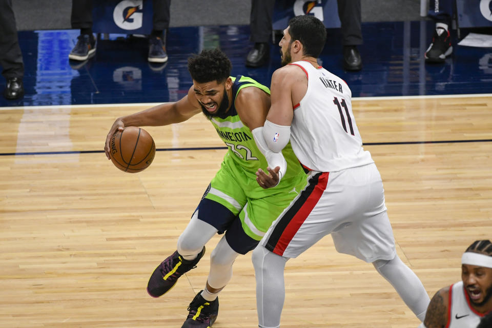 Minnesota Timberwolves center Karl-Anthony Towns (32) drives past Portland Trail Blazers center Enes Kanter(11) during the first half of an NBA basketball game Saturday, March 13, 2021, in Minneapolis. (AP Photo/Craig Lassig)