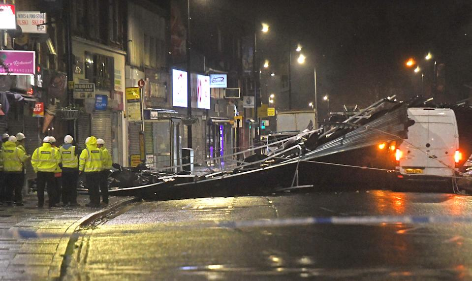 Construction workers in Slough high street after a roof was blown off a building onto the road amid strong winds which have battered parts of the UK.