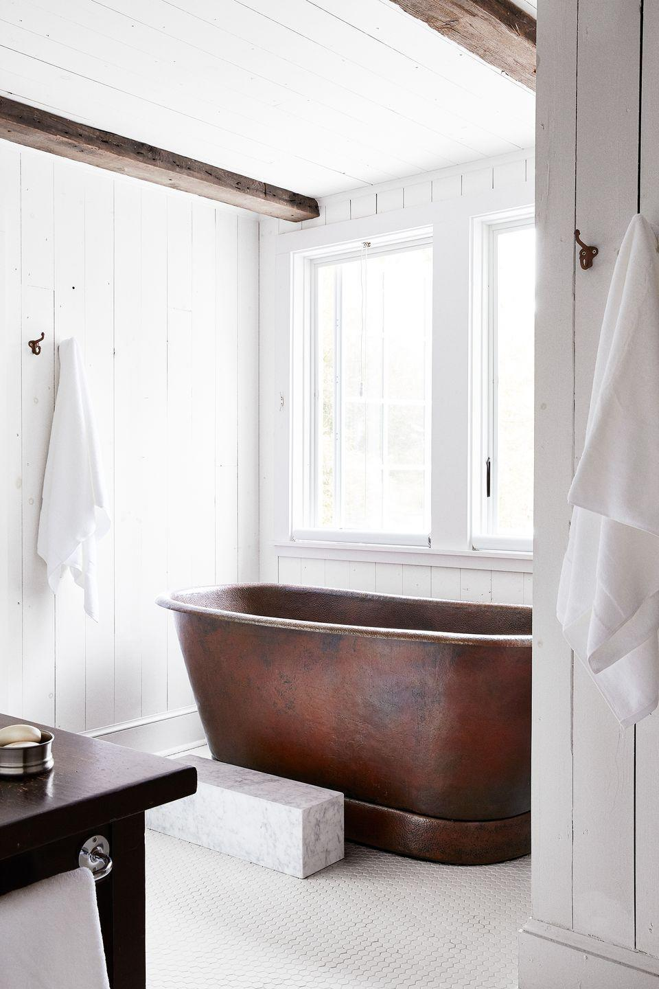 <p>Brighten up a bathroom by covering every surface in white paint and tiles, but keep the country chic elements alive by sparing the exposed beams and opting for a grand copper bathtub. </p>