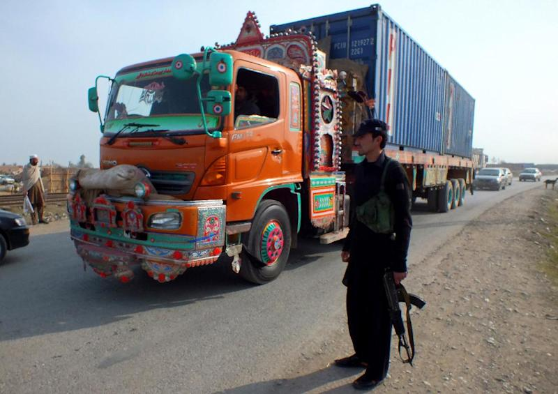 A Pakistani tribal policeman stands guard along a road used by NATO trucks as they reportedly bring supplies from neighboring Afghanistan in Jamrud, in the tribal area of Khyber, Pakistan, on Monday, Feb. 11, 2013. The U.S. says it has started using the land route through Pakistan to pull American military equipment out of Afghanistan. (AP Photo/Jibran Yousufzai)