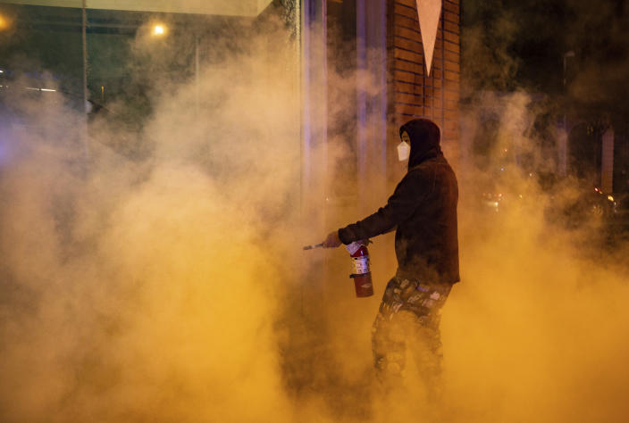 Demonstrators set fire to the front of the California Bank and Trust building during a protest against police brutality in Oakland, Calif., on Friday, April 16, 2021. (AP Photo/Ethan Swope)