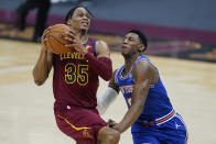Cleveland Cavaliers' Isaac Okoro, left, drives to the basket against New York Knicks' RJ Barrett during the first half of an NBA basketball game, Friday, Jan. 15, 2021, in Cleveland. (AP Photo/Tony Dejak)