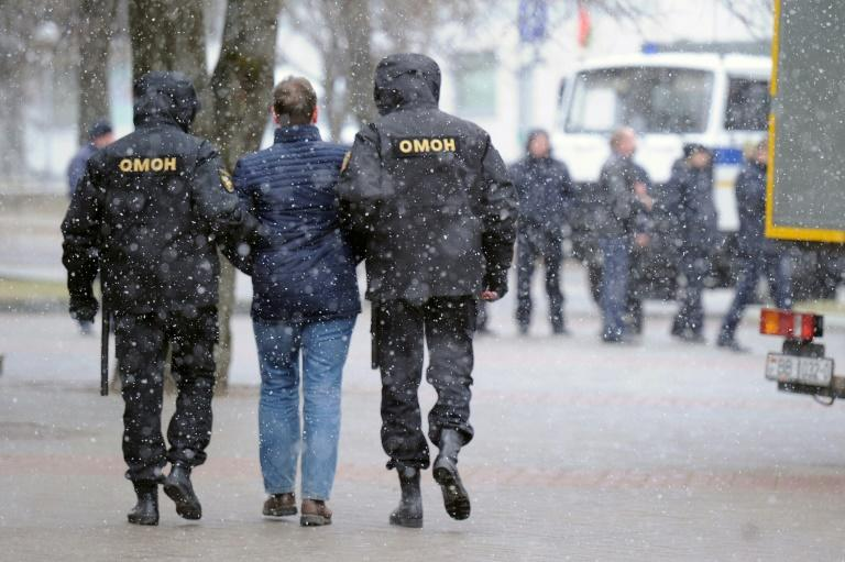 """Police officers detain a man as opposition supporters gather for a rally against President Alexander Lukashenko's rule and a controversial new tax on """"spongers"""" - those who work less than six months a year - in Minsk on March 25, 2017"""