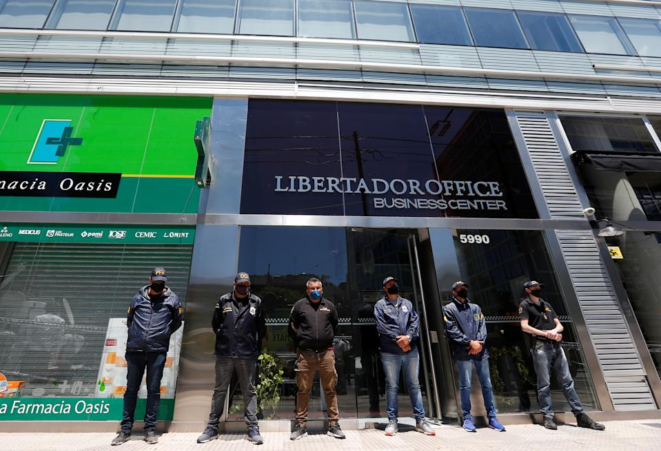 Police officers stand guard outside the building where Leopoldo Luque, the personal doctor of late soccer legend Diego Maradona, has his office in Buenos Aires. (Reuters/Agustin Marcarian)