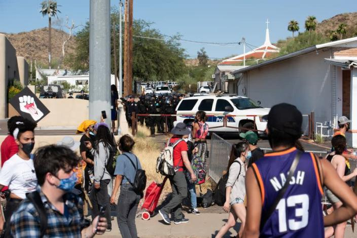 Police file down an ally towards protestors during the visit by U.S. President Donald Trump to the Dream City Church in Phoenix