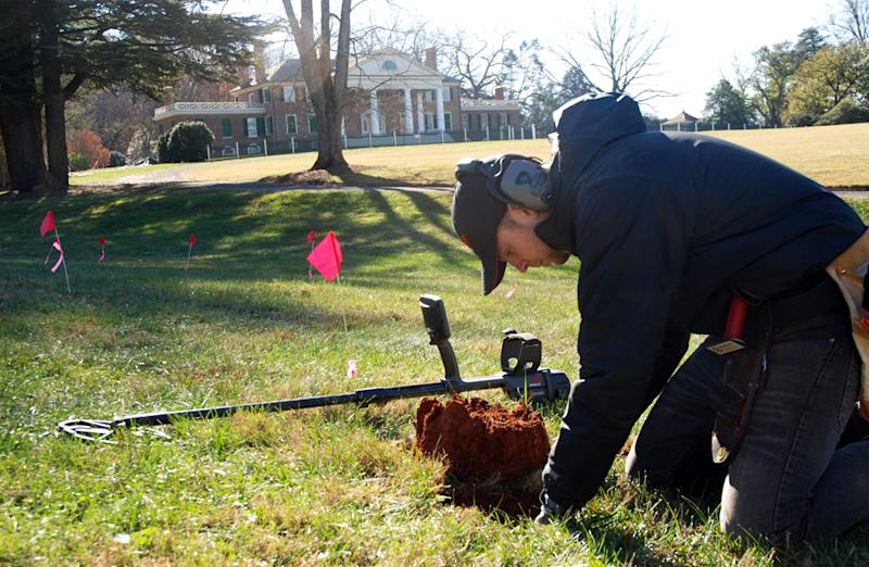 CORRECTS DATE OF PHOTO TO NOV. 14 NOT 15, AND LOCATION TO ORANGE, NOT MONPELIER, VA. - In this Thursday, Nov. 14, 2013, photo, Errol Belda, 26, of Bend, Ore., digs for an artifact after using a metal detector to survey land in the shadow of James Madison's Montpelier, in Orange, Va. Archaeologists and metal-detecting hobbyists are teaming up to unearth the history that lies beneath the 2,650-acre Virginia estate dating back to the 18th century. The blips and beeps of the high-tech devices have helped rediscover historic sites the plantation belonging to the nation's fourth president, including slave quarters, Civil War camps, a blacksmith's workshop and old tobacco barns. (AP Photo/Michael Felberbaum)