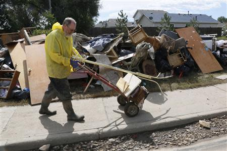 Mark Brothe wheels out more possessions damaged by a flood to add to a pile in front of his house, in Evans, Colorado September 23, 2013. REUTERS/Rick Wilking