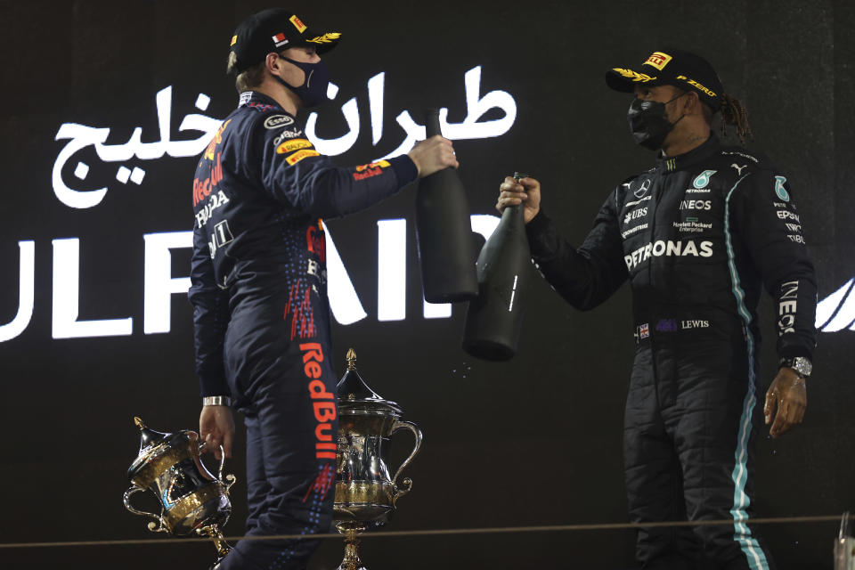 Mercedes driver Lewis Hamilton of Britain, winner, right, celebrates with Red Bull driver Max Verstappen of the Netherlands on the podium after the Bahrain Formula One Grand Prix at the Bahrain International Circuit in Sakhir, Bahrain, Sunday, March 28, 2021. (Lars Baron, Pool via AP)