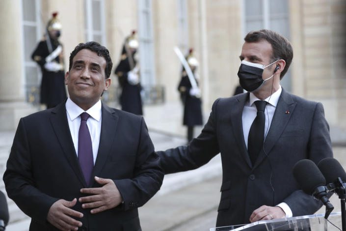 French President Emmanuel Macron, right, and Mohammad Younes Menfi, president of Libya's Presidential Council, left, after a meeting, at the Elysee Palace, in Paris, Tuesday, March 23, 2021. Macron said France will reopen its embassy in Libya's capital Tripoli on Monday as a gesture of support for the new interim government. (AP Photo/Thibault Camus)