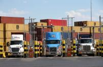 FILE PHOTO: Trucks loaded with shipping containers leave the Port of Montreal