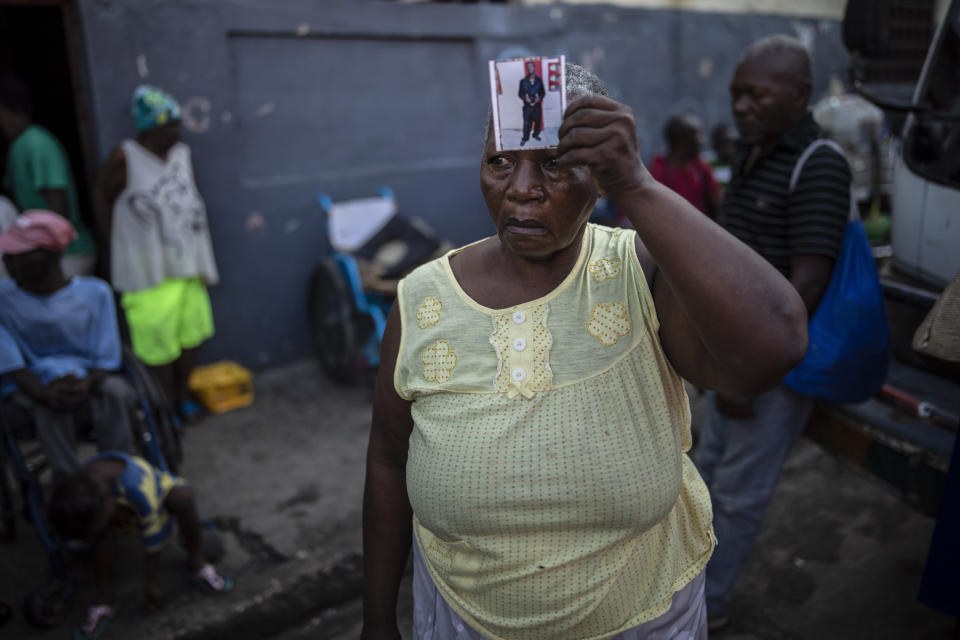 """Twice displaced due to the country's escalating violence, Marie Jaquesmal poses with a portrait of her son Michel, who went missing during an assault lead by police, in Port-au-Prince, Haiti, Thursday, Sept. 16, 2021. With 139 houses set fire behind her, she lost track of her 28-year-old son, who is deaf and cannot speak. """"I don't know if he is dead or alive, the only thing I saw is that those men were policemen."""" (AP Photo/Rodrigo Abd)"""