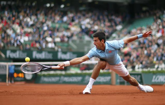 Novak Djokovic of Serbia hits a return to Joao Sousa of Portugal during their men's singles match at the French Open tennis tournament at the Roland Garros stadium in Paris May 26, 2014. REUTERS/Gonzalo Fuentes (FRANCE - Tags: SPORT TENNIS TPX IMAGES OF THE DAY)