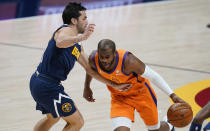 Phoenix Suns guard Chris Paul drives past Denver Nuggets guard Facundo Campazzo during the first half of an NBA basketball game Friday, Jan. 1, 2021, in Denver. (AP Photo/David Zalubowski)