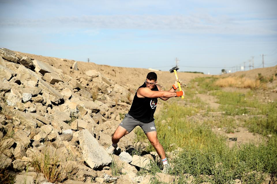 TULARE, CALIFORNIA - JUNE 06:  Olympic hopeful boxer Richard Torrez Jr. smashes cement with a sledge hammer during a training session on June 06, 2020 in Tulare, California. Torrez Jr. was one of 13 boxers selected to represent Team USA at the Tokyo 2020 Olympic Games Boxing Qualifiers in Argentina, but the qualifier was canceled due to the coronavirus. The 20-year-old has won numerous international tournaments, and is currently ranked fifth in the world in the super heavyweight weight class. The training center in Colorado is currently closed so Torrez Jr. continues to train at home with his father, who is his coach. His father has implemented many different types of training methods, such as hitting cement rocks with a sledge hammer, filling up wheel barrels with sand, and flipping over tractor tires. Athletes across the globe are now training in isolation under strict policies in place due to the Covid-19 pandemic.  (Photo by Ezra Shaw/Getty Images)
