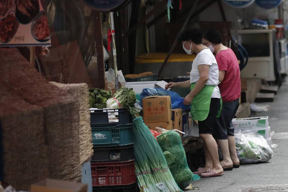 People wearing face masks as a precaution against the coronavirus talk at a local market in Seoul, South Korea, Saturday, Aug. 29, 2020. Health officials prepare to tighten distancing restrictions in the greater capital area. (AP Photo/Lee Jin-man)