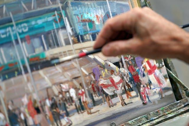 An artist paints a picture of Wembley Stadium ahead of the Euro 2020 final
