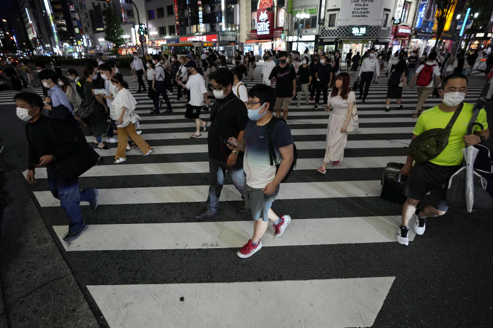 People walk along a pedestrian crossing Friday, July 30, 2021, in Tokyo, as Japanese Prime Minister Yoshihide Suga expanded a coronavirus state of emergency to four more areas in addition to Tokyo following record spikes in infections as the capital hosts the Olympics. (AP Photo/Eugene Hoshiko)