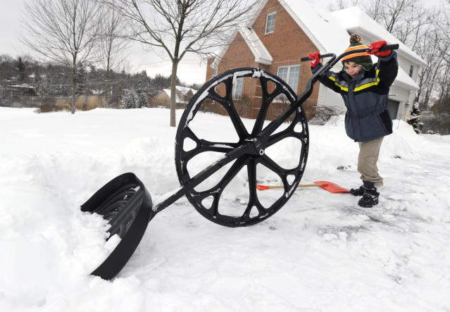 "Nathan Lee, 5, uses a ""wovel"" to remove snow from his driveway along Megan Drive, in State College, Pa. A major winter storm hit Centre County Wednesday and the clean up continues Thursday, Dec. 27, 2012. (AP Photo/Centre Daily Times, Nabil K. Mark)"