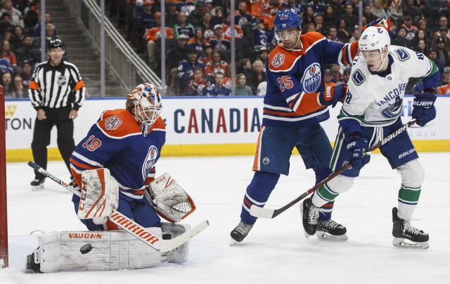 Vancouver Canucks' Adam Gaudette (88) and Edmonton Oilers' Darnell Nurse (25) watch as Oilers goalie Mikko Koskinen (19) makes a save during the first period of an NHL hockey game Thursday, March 7, 2019, in Edmonton, Alberta. (Jason Franson/The Canadian Press via AP)