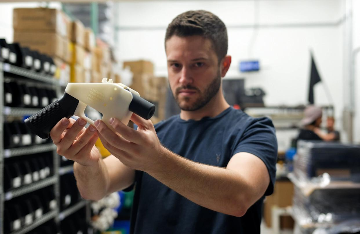Cody Wilson poses with a 3D-printed gun in his factory in Austin, Texas, on Aug. 1, 2018. Austin authorities charged Wilson with sexually assaulting a child on Wednesday. (Photo: KELLY WEST via Getty Images)