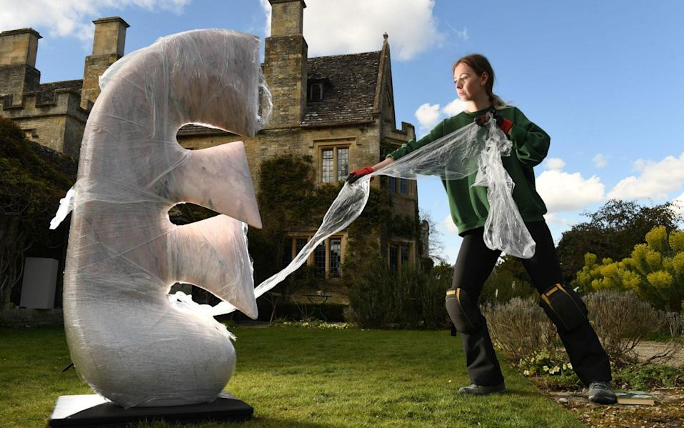 Gardener Danielle Falkingham prepares the lawns and flower beds of 17th-century Asthall Manor in Oxfordshire for its tenth biennial sculpture show, OnForm - Russell Sach