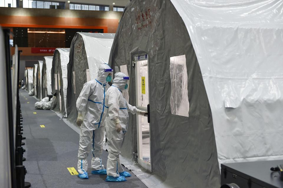 """Staff checking a unit at a temporary """"Fire Eye"""" laboratory used for coronavirus testing in Nanjing (AFP via Getty Images)"""