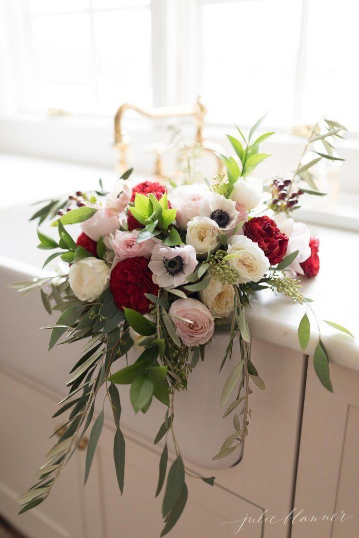 "<p>This gorgeous, understated combination of ivory, pink and red roses and anemones, accented with seeded eucalyptus, would suit equally well as your bouquet or as a stunning centerpiece. </p><p><strong>See more at <a href=""https://julieblanner.com/christmas-arrangements/"" rel=""nofollow noopener"" target=""_blank"" data-ylk=""slk:Julie Blanner"" class=""link rapid-noclick-resp"">Julie Blanner</a>.</strong></p>"