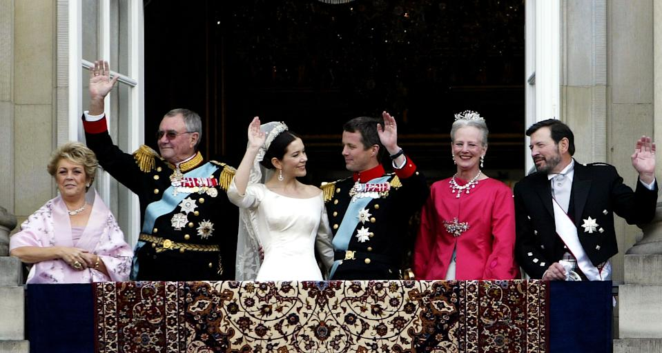 COPENHAGEN, DENMARK - MAY 14:  Crown Princess Mary and Crown Prince Frederik, (C) Queen Margrethe II of Denmark and Prince Henrik (2L and 2R), Mary's father John Donaldson (R) and his wife Susan Moody (L) wave to the crowd on the balcony of Christian VII's Palace after the wedding on May 14, 2004 in Copenhagen, Denmark. The romance began in 2000 when Miss Mary Elizabeth Donaldson met the heir to one of Europe's oldest monarchies over drinks at the Sydney Olympics, where he was with the Danish sailing team. (Photo by Ian Waldie/Getty Images)